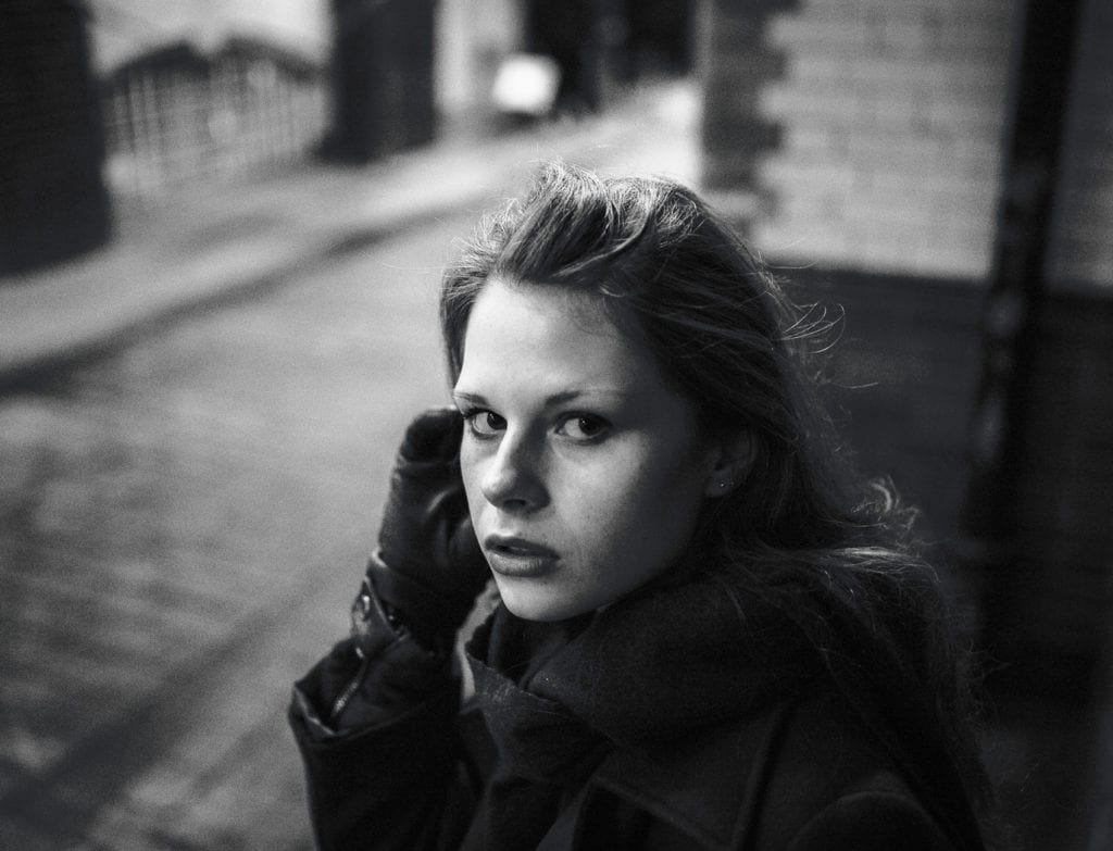 A black and white photograph of a woman on a London street looking at the camera