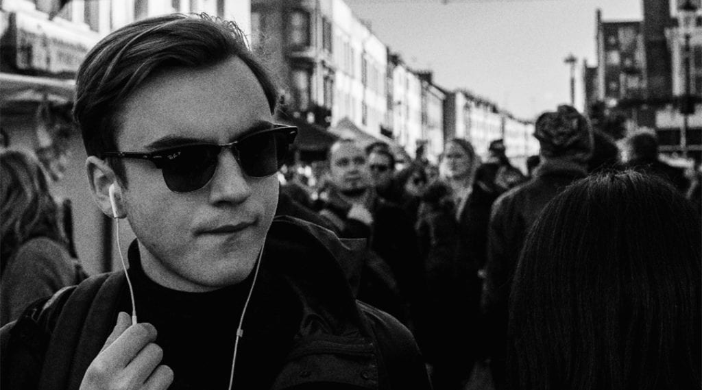 A black and white photograph of a man walking along the street, wearing ray ban sunglasses