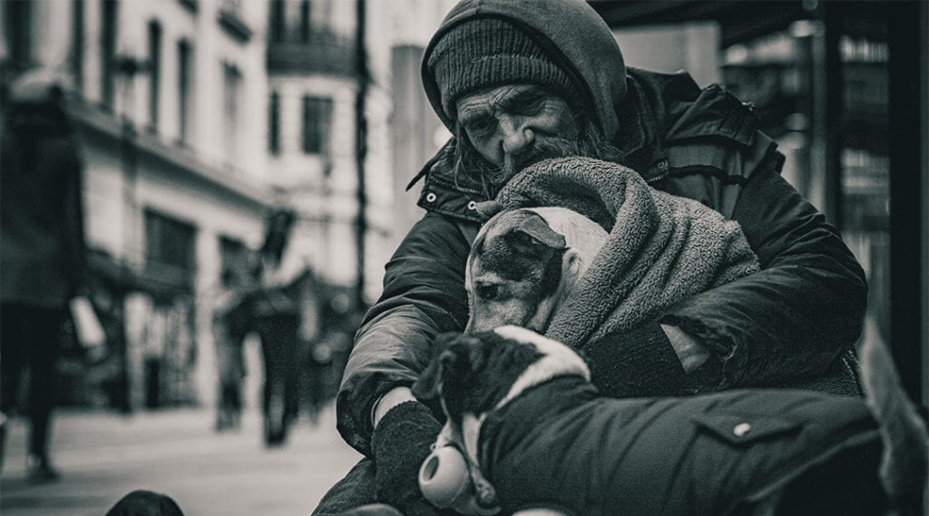 A black and white photograph of a man holding a dog as he sits on a London street