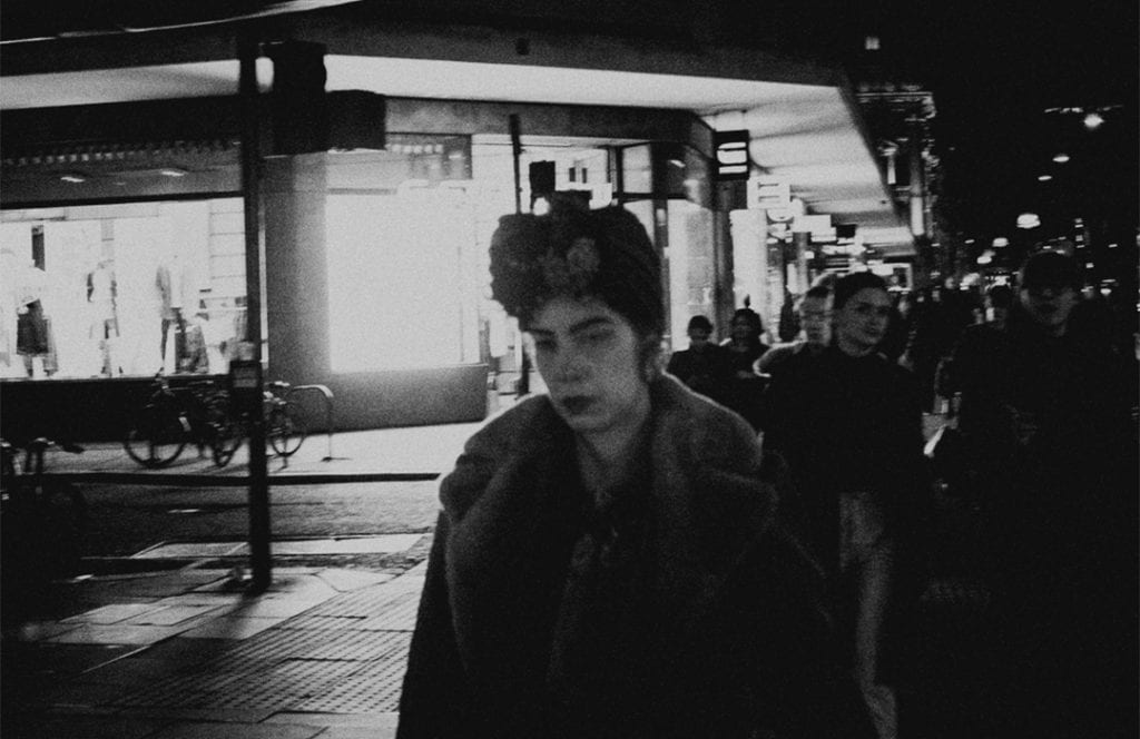 a black and white photograph of a woman walking down a street at night