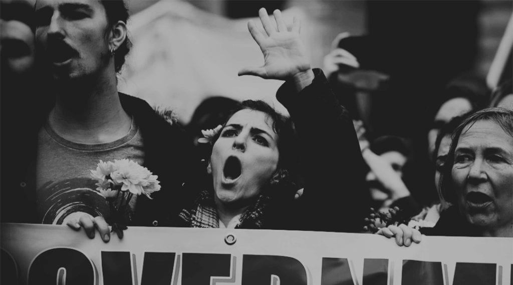 A black and white photograph of a woman at the front of a street protest