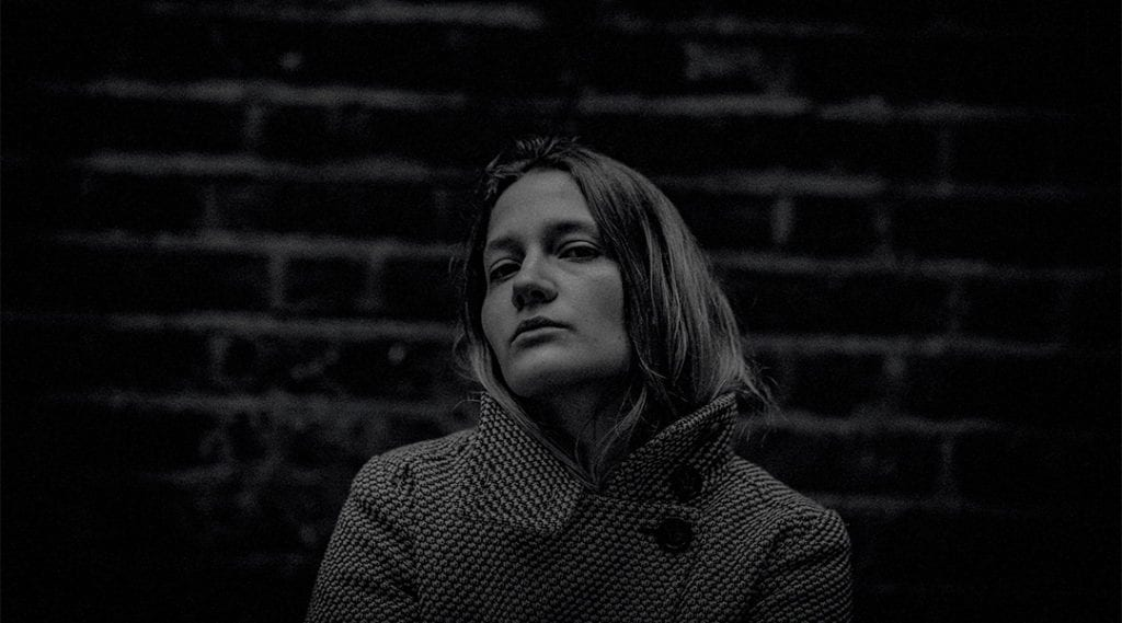 A black and white picture of a woman in a jacket in front of a wall