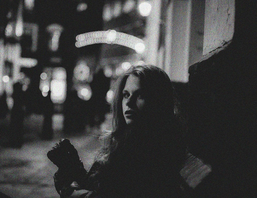 A black and white image of a woman sitting on the street looking at the camera