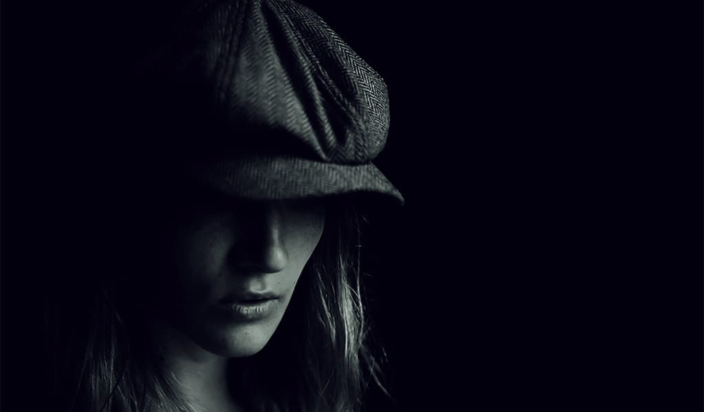 A black and white film photograph of a woman wearing a flat cap