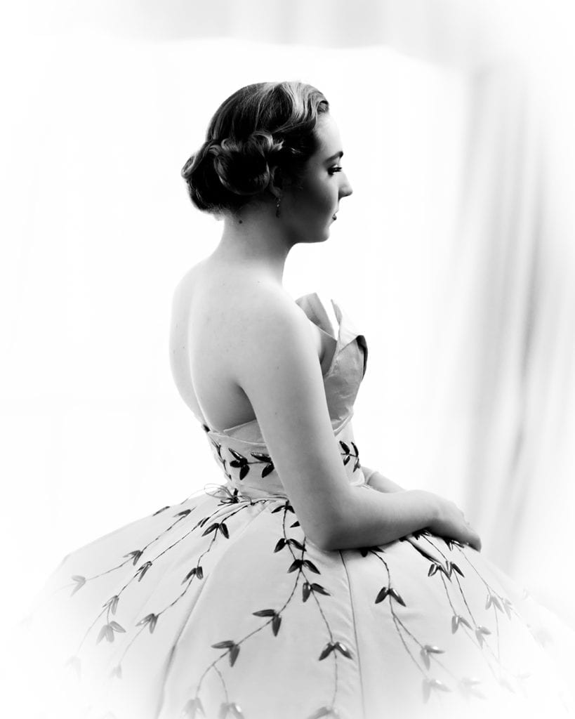 A black and white photograph of a woman in a ball gown