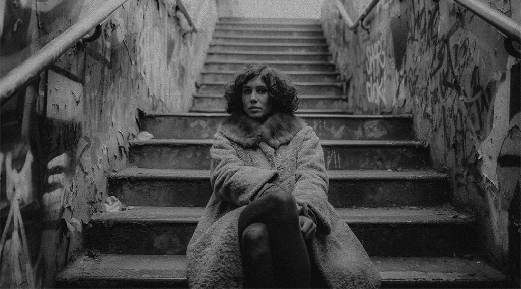 A black and white photograph of a woman, wearing a jacket, sitting on dirty steps