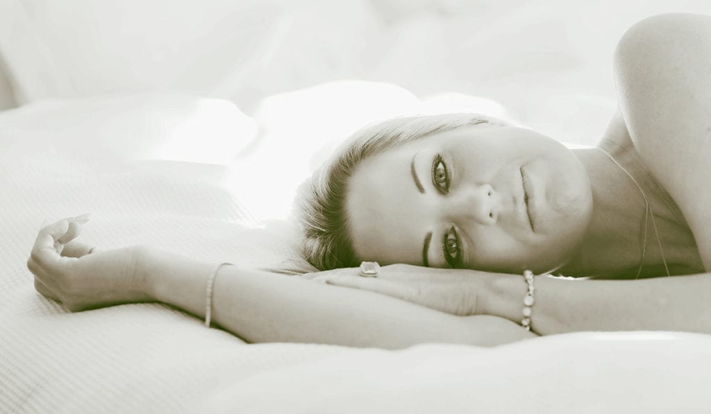 A woman lies on her bed, looking back at the camera