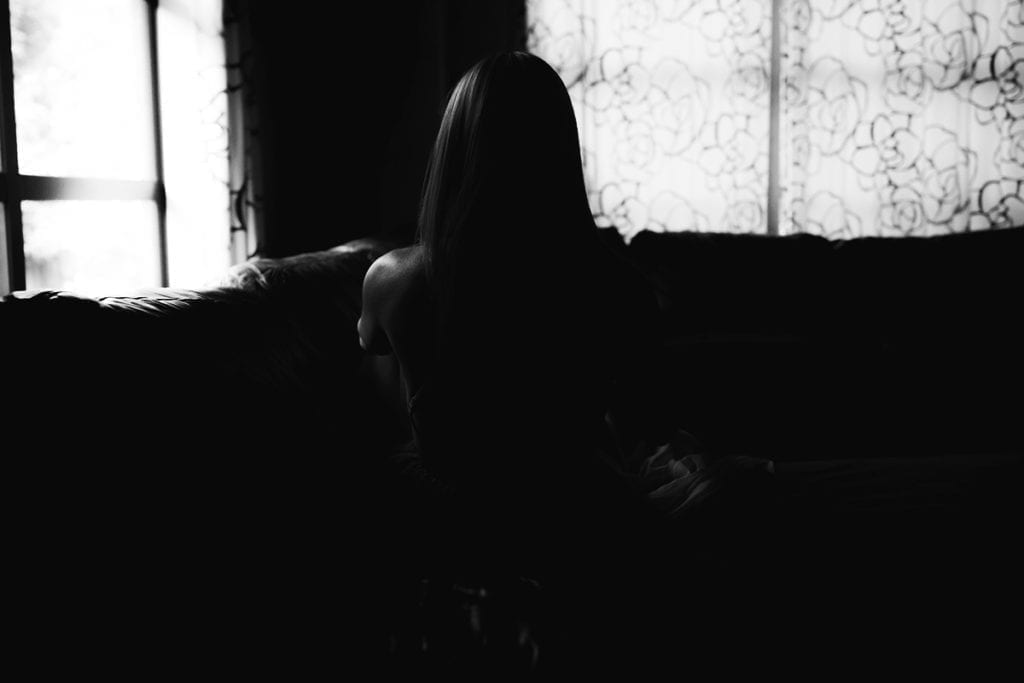 A black and white silhouette of a woman on a sofa