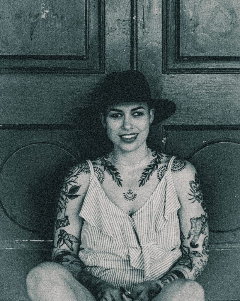 A black and white close up photograph of a woman with many tattoos