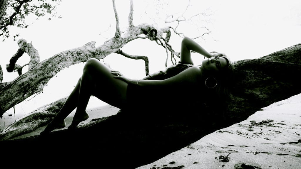 A black and white photo of a woman lying back on a tree on a beach