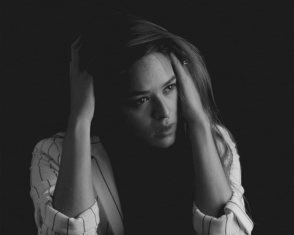 A woman sits in near darkness, holding the sides of her head, captured in black and white