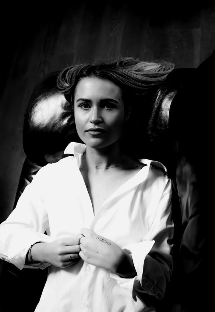 a woman on a leather sofa wearing a white shirt