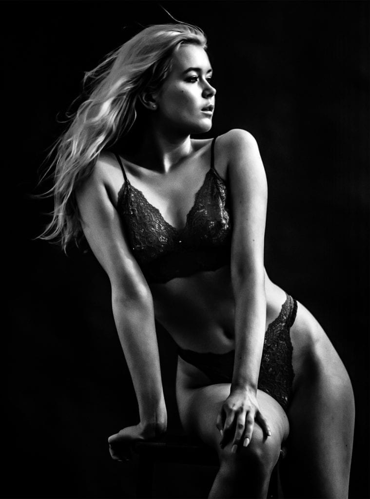 A black and white photograph of a woman sitting on a chair as she wears dark lingerie