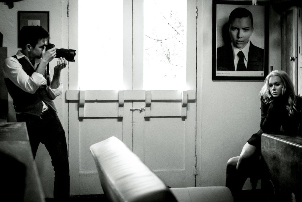 A man holding a camera takes a photo of a woman sat on the other side of the room