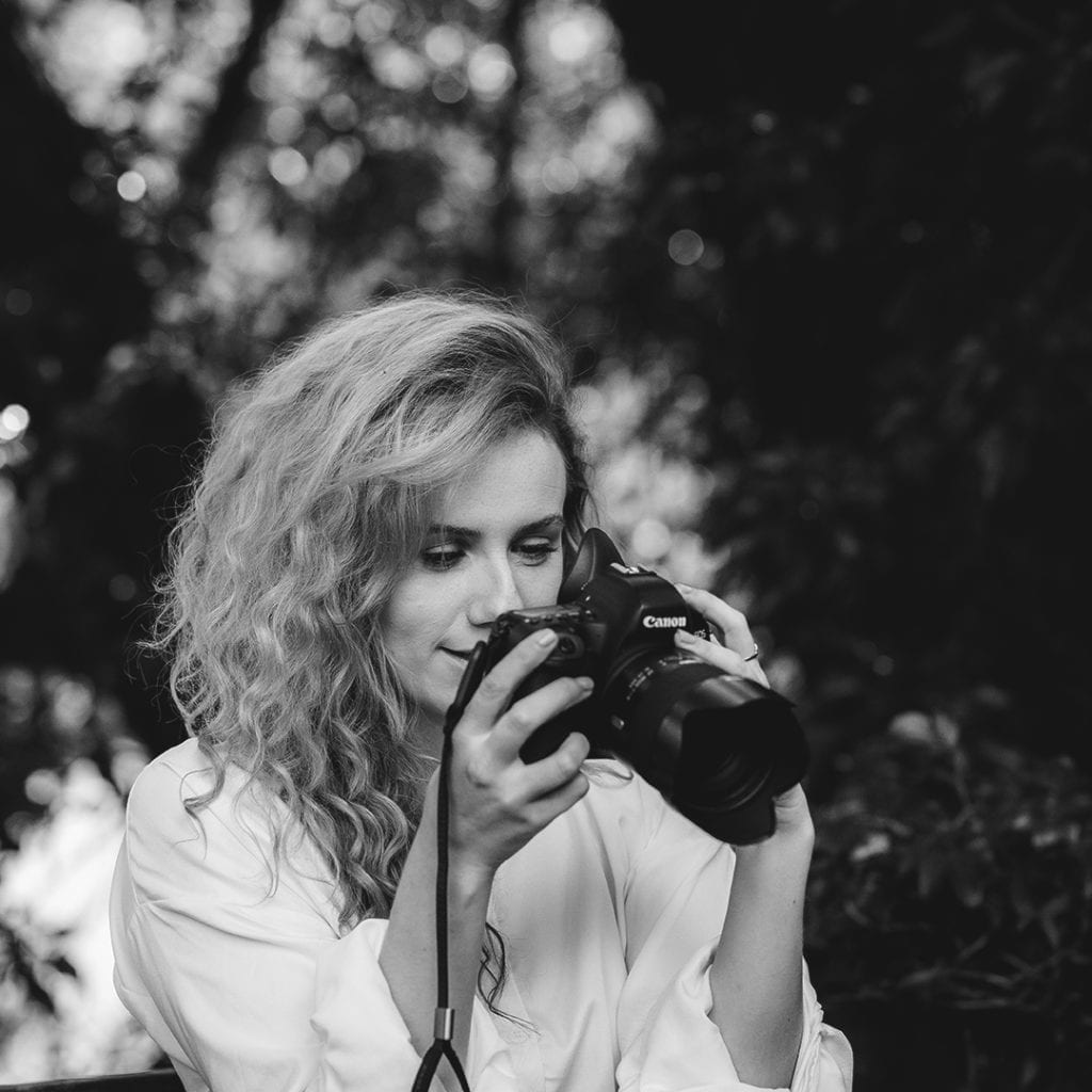 A black and white photograph of a woman in a white t shirt holding a camera looking at the back