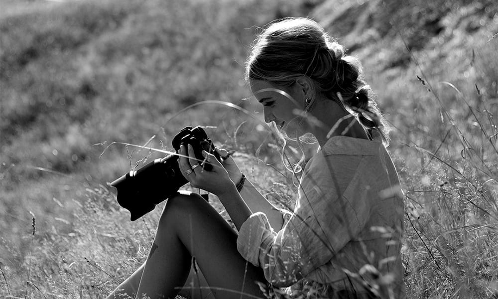 A black and white photograph of a woman sitting in long grass as she holds a camera