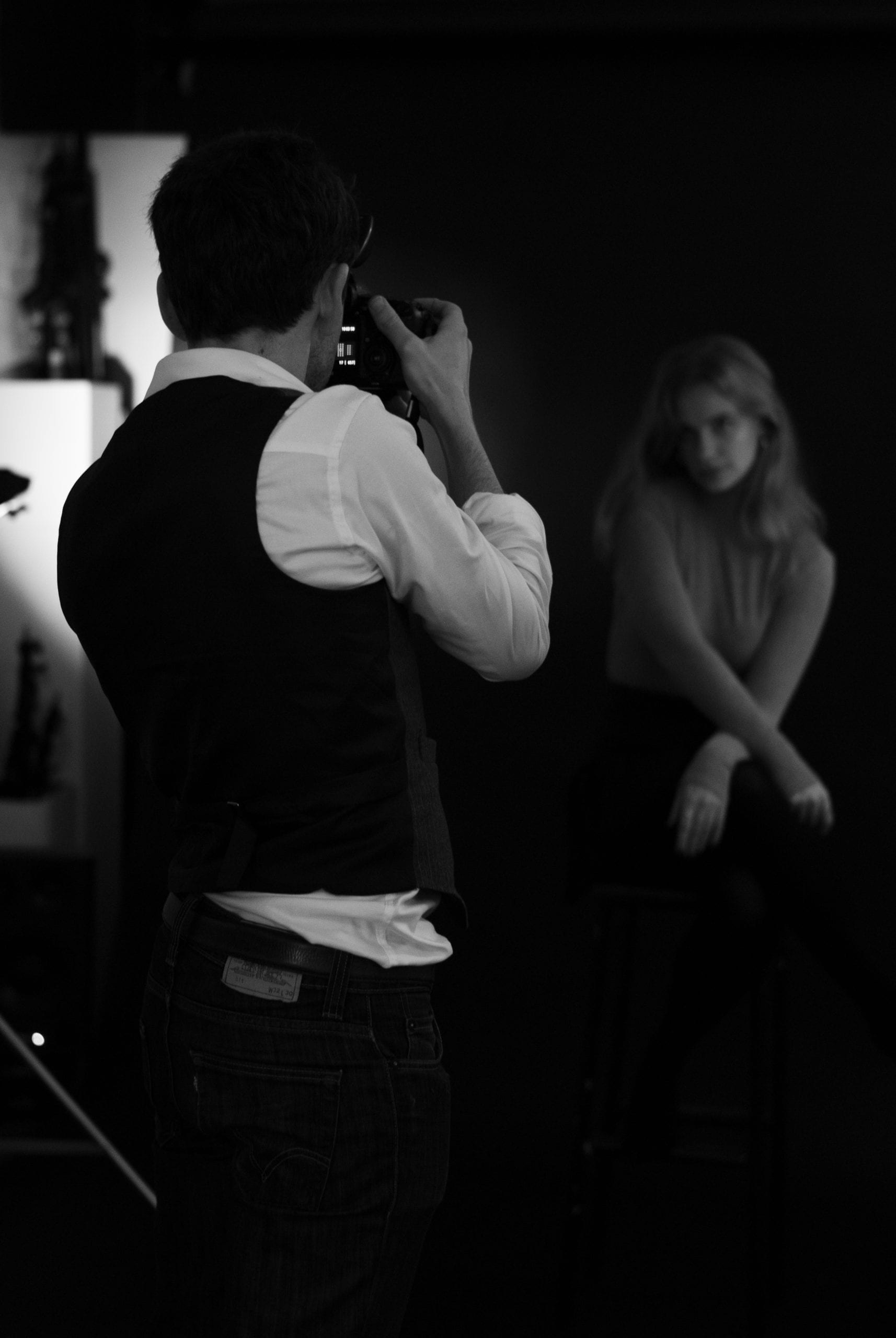 A man holding a camera takes a photo of a woman in a photo studio