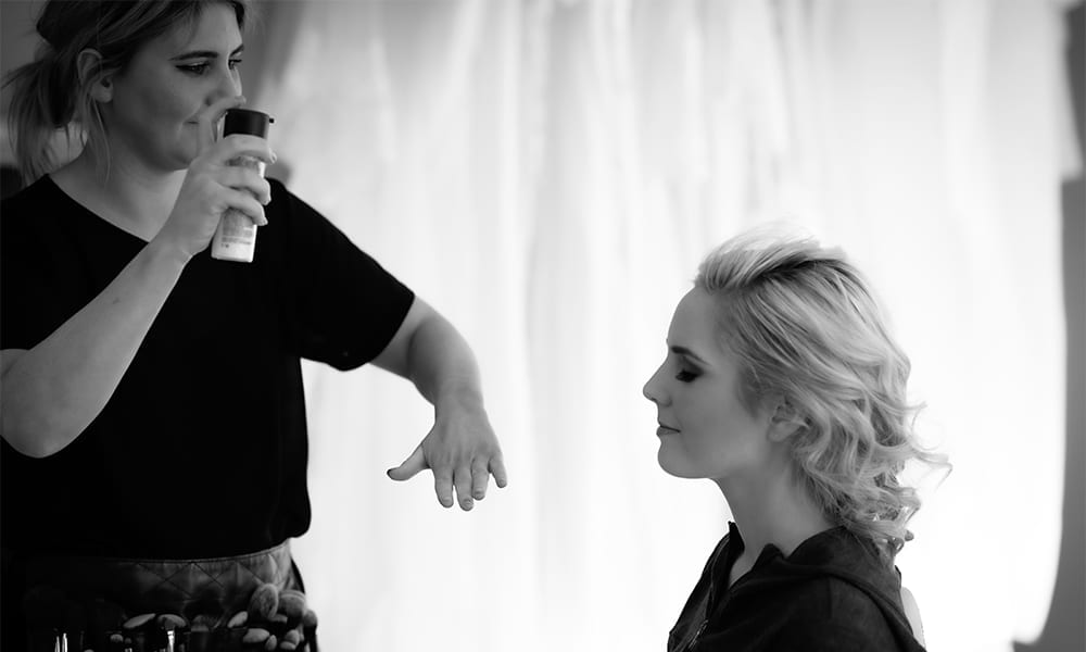 A black and white photograph of a woman spraying hair spray on a woman with blonde hair