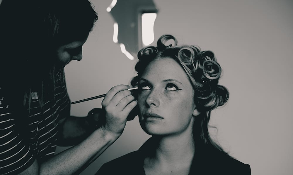 A black and white photograph of a woman with hair in curls getting her make up done