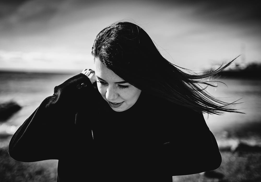 A black and white photograph of a woman standing on the edge of a beach
