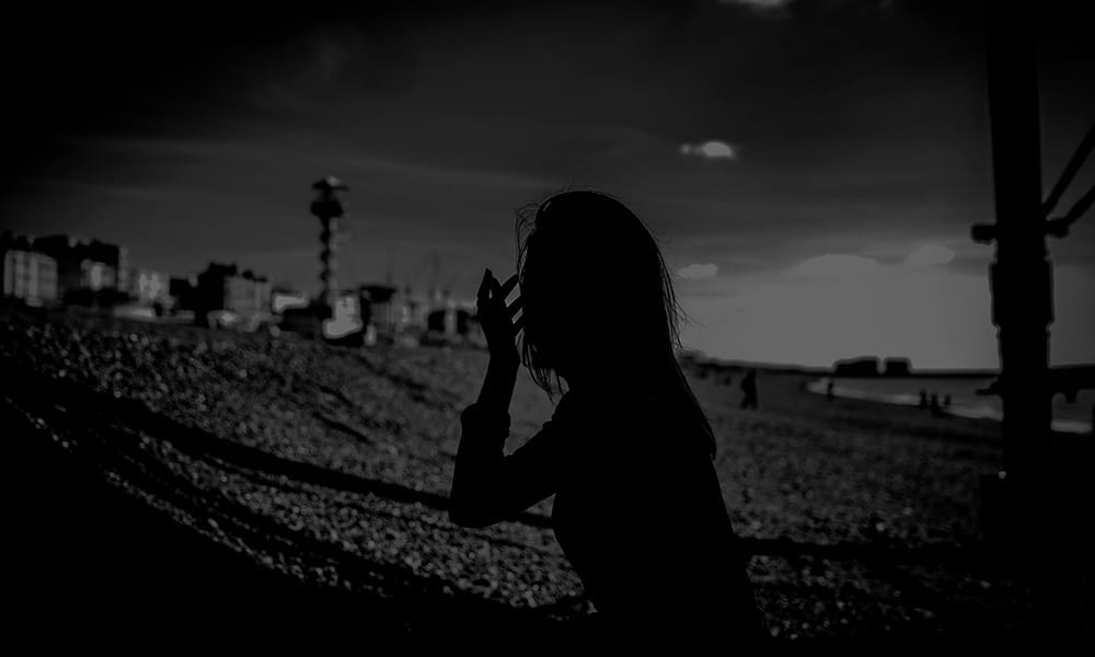 A silhouette black and white photograph of a woman under a pier