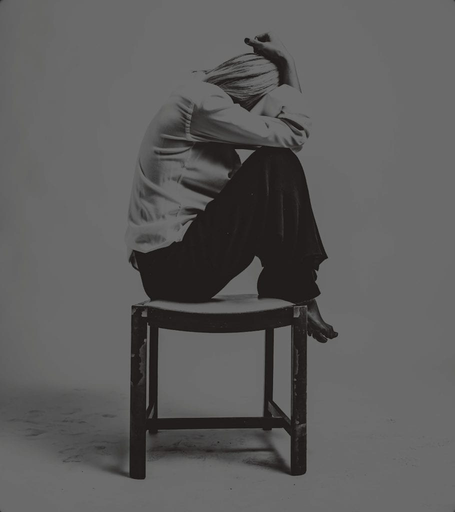 a black and white photo of a woman sitting on a chair, crouched up