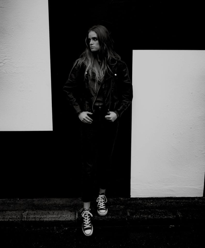 A black and white photograph of a woman standing with her feet on the edge of a pavement