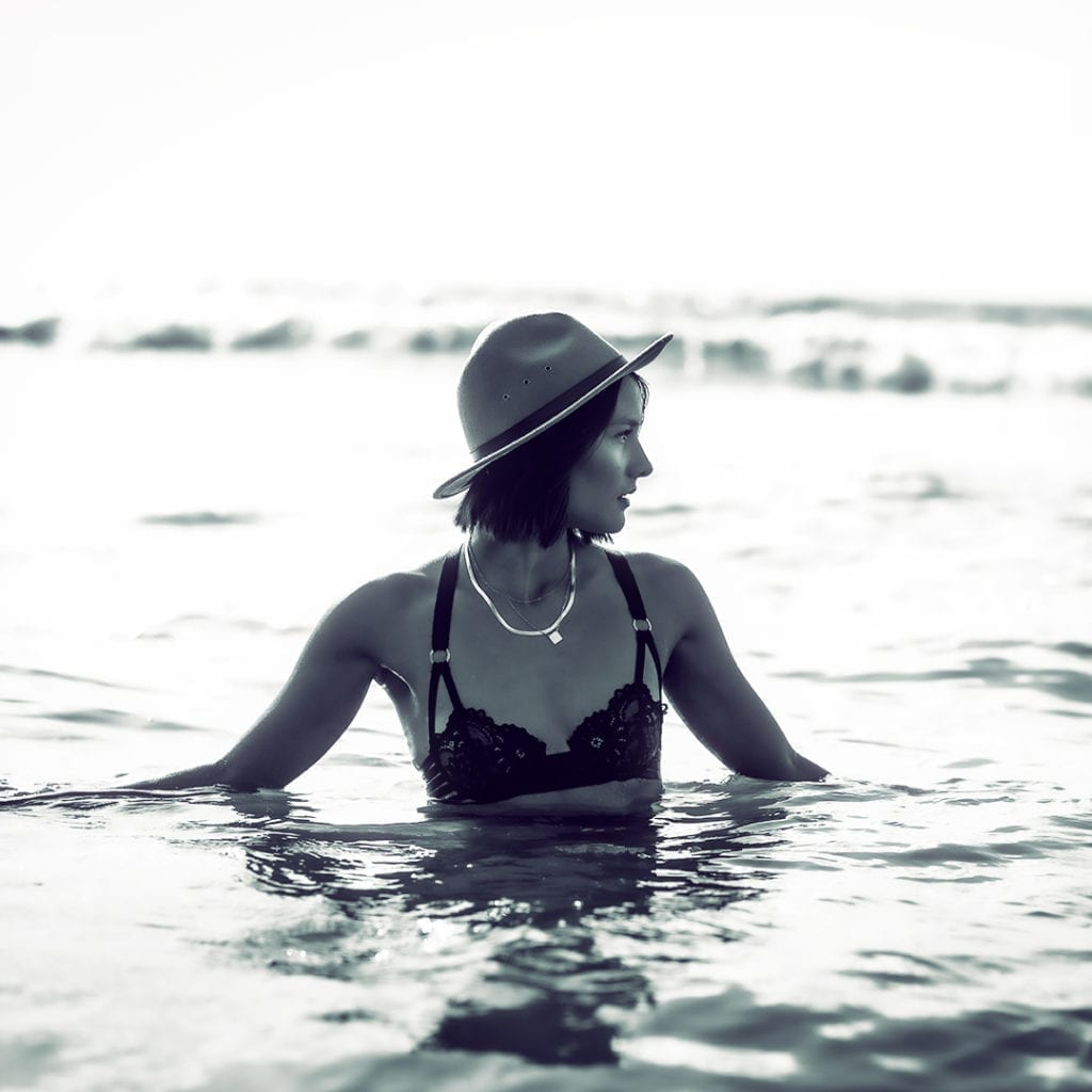 a woman sits in the water whilst wearing a hat