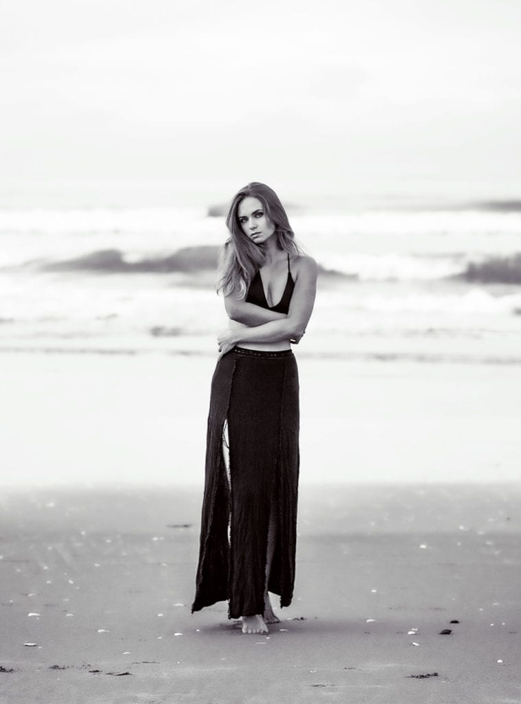 a woman in a black top on a beach looking at the camera