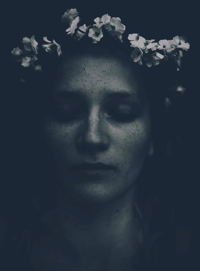 A black and white photo of a woman with flowers on her head
