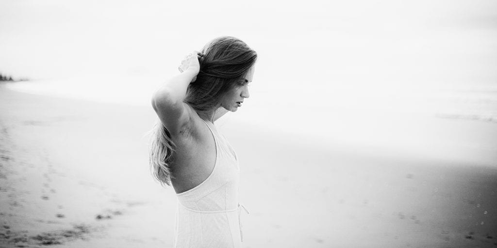 a black and white photo of a woman in a white dress standing on a beach looking down