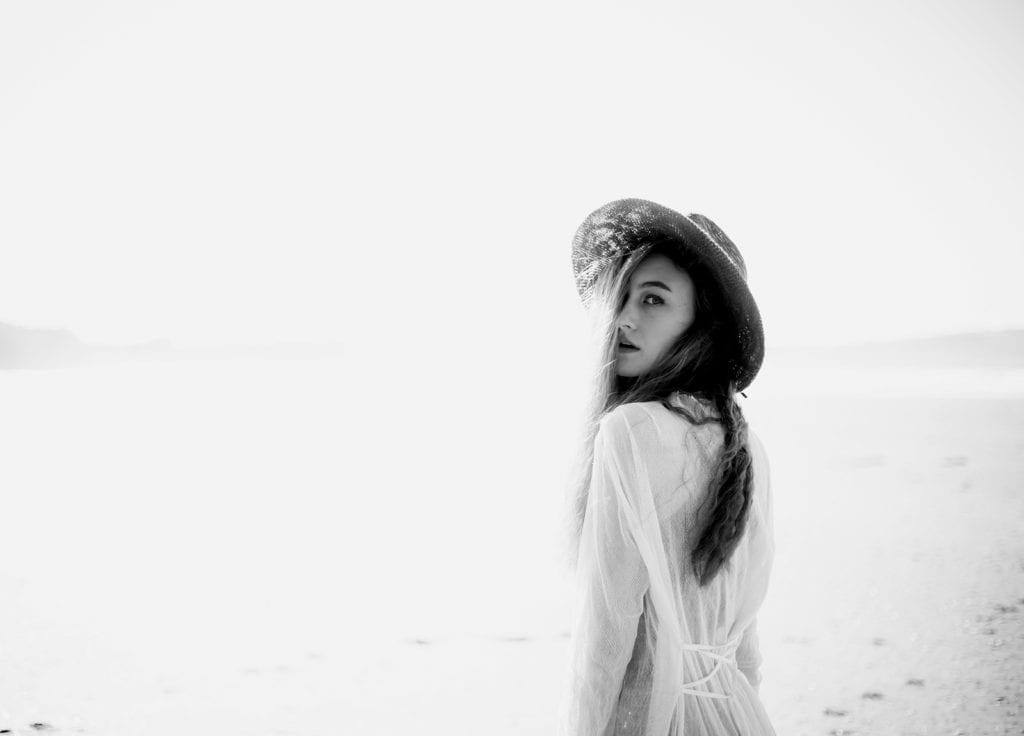 A black and white photo of a woman in a white gown standing on a beach