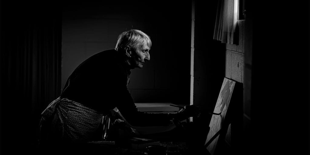 A black and white photo of an artist leaning forward with a paint brush
