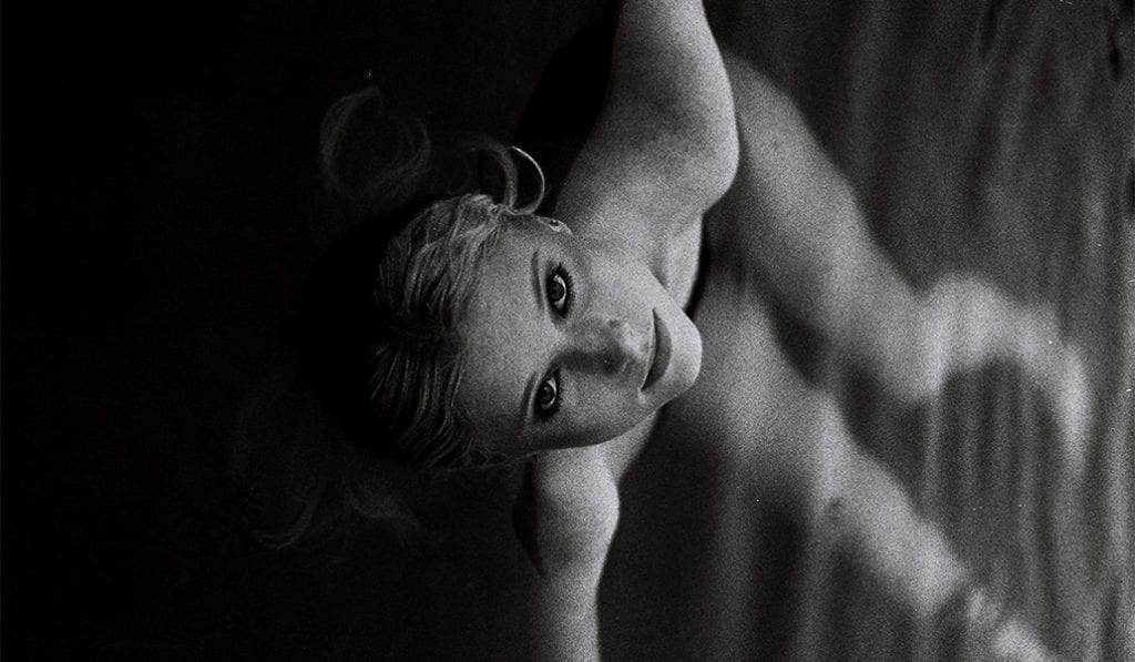 black and white photo of a woman lying in water looking back and looking up