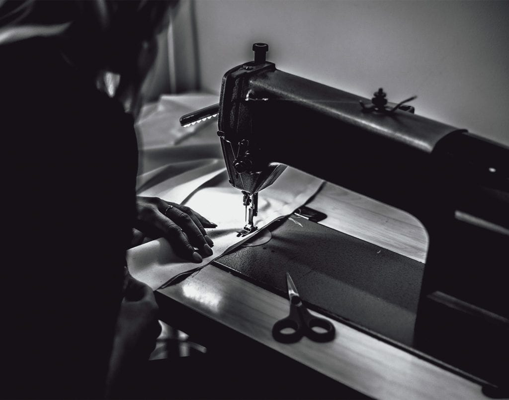 A black and white photo of a woman using a sewing machine