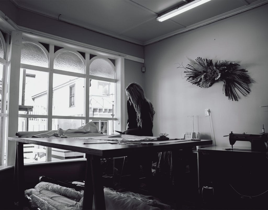 A black and white picture of a woman standing at a table cutting fabric