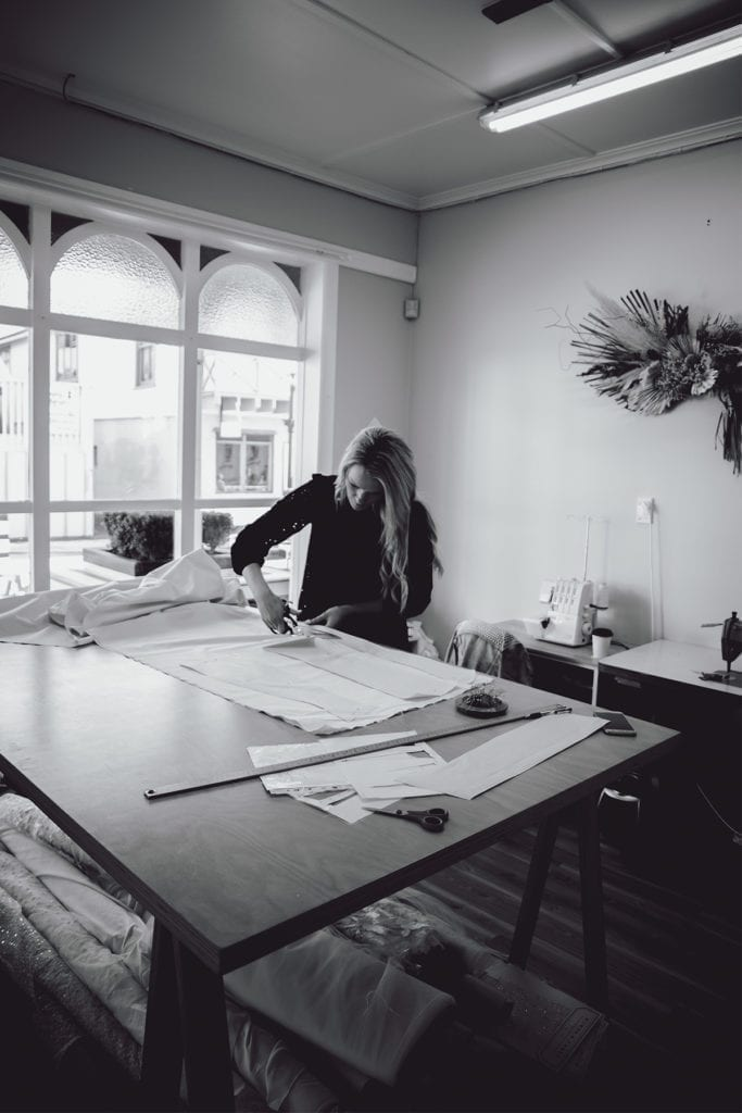 a black and white picture of a woman cutting fabric