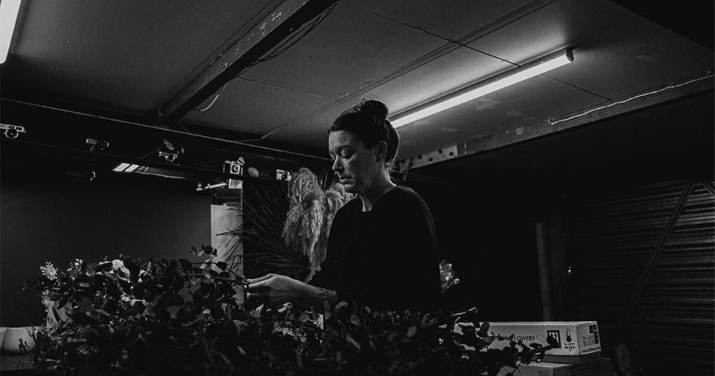 a black and white picture of a woman working on flowers in a garage
