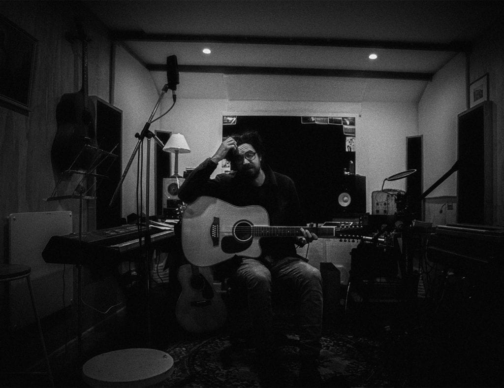 A black and white photo of a man holding a guitar and scratching his head as he sits on a chair in a dark room