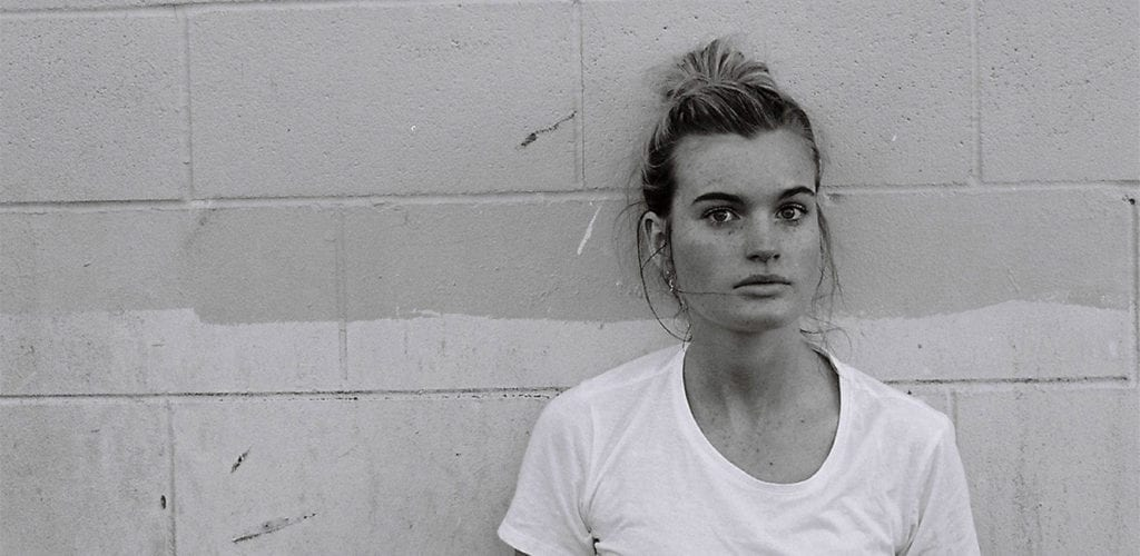 a black and white photo of a woman in a white t shirt with the woman leaning against a wall