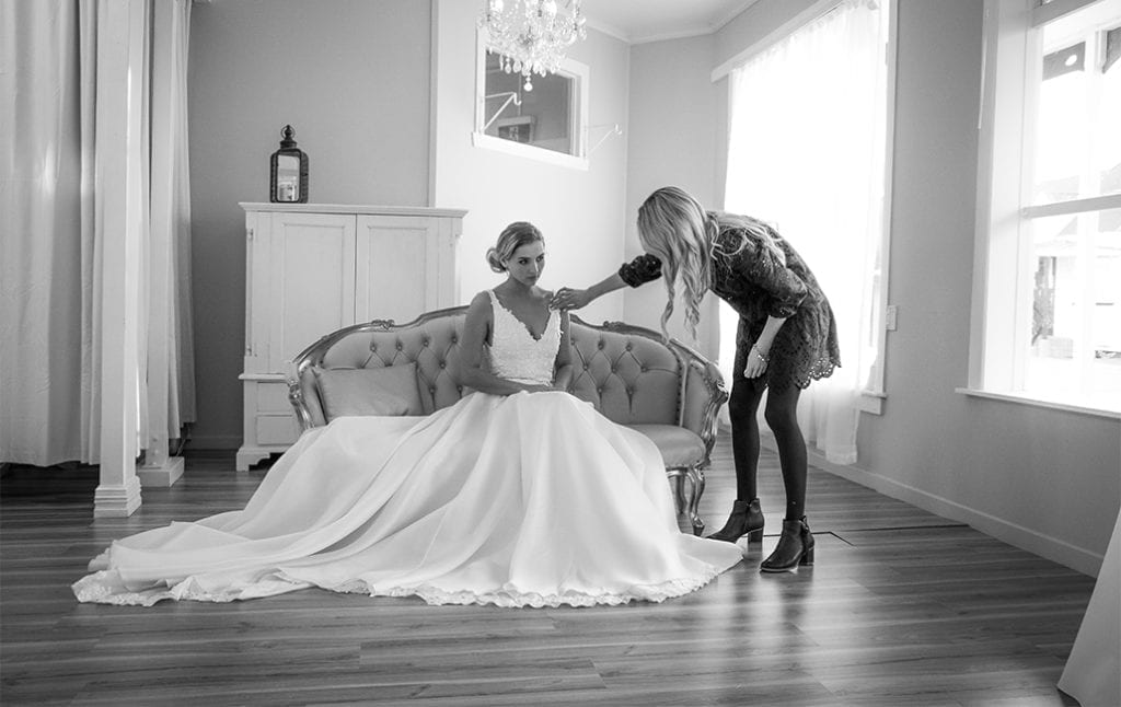 a black and white photo of a woman in a dark dress adjusting a bridal gown worn by a woman sat on a sofa
