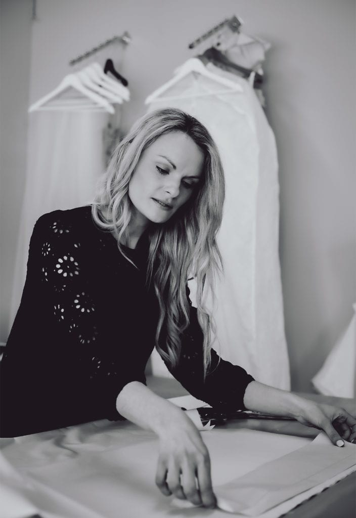 A black and white photo of a woman standing at a desk as she works on a bridal gown