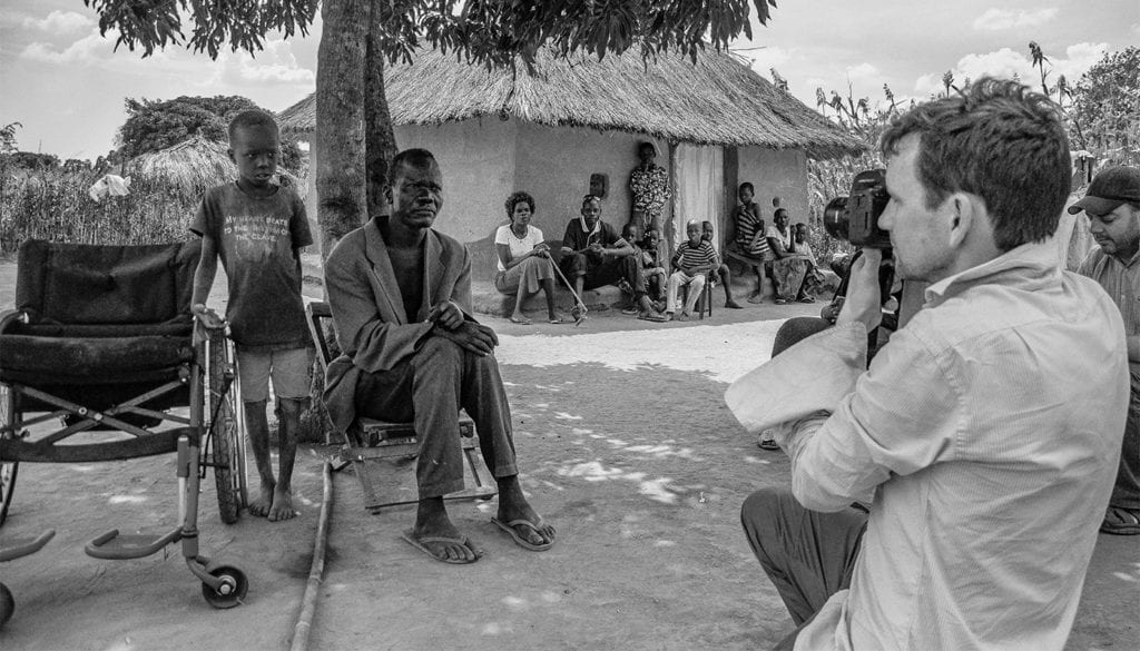 A black and white photo of a man in a wheelchair near a hut with a man taking his photograph as people watch